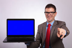 Young business man presents a laptop and points at you Stock Photography