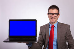 Young business man presents laptop while smiling Stock Image
