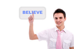 Young business man pressing the believe key Royalty Free Stock Photo