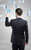 Young business man pressing a touchscreen button Stock Photo