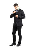Young business man putting cellphone in his suit jacket inner pocket. Stock Photos