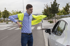 Young business man putting on reflective vest outside car Royalty Free Stock Image