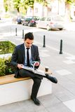 Young Business Man Reading Book While Drinks Coffee Outdoor. And Sitting At Bench Stock Photo