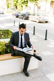 Young Business Man Reading Book While Drinks Coffee Outdoor. And Sitting At Bench Stock Photos