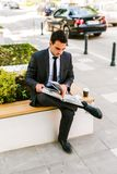 Young Business Man Reading Book While Drinks Coffee Outdoor. And Sitting At Bench Stock Photography