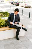 Young Business Man Reading Book While Drinks Coffee Outdoor. And Sitting At Bench Royalty Free Stock Photos