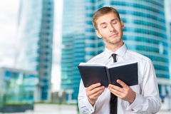 Young business man reading a book Stock Photos