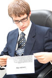 Young business man reading a curriculum vitae. Sitting on a chair royalty free stock photography