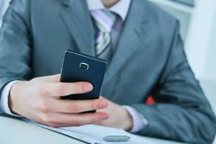 Young business man reading message with smartphone in office. Stock Photography