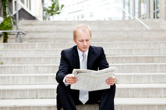 Young business man is reading newspaper outdoor Royalty Free Stock Photos