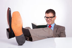 Young business man reads a book with feet on desk Royalty Free Stock Photo