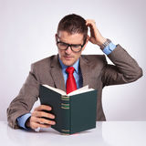 Young business man reads a book and scratches his head Royalty Free Stock Photos