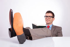Young business man reads with feet on desk Royalty Free Stock Photography