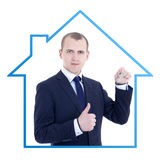 Young business man realtor with key in hand thumbs up  o Royalty Free Stock Images