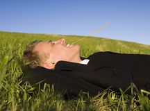 Young business man relaxing. A young business man relaxing on the grass under clear blue sky royalty free stock photos