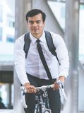 Business man is riding bicycle to work in the city. Young Business man is riding bicycle to work in the city stock photo