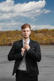 Young business man on roof top. Young ginger looking man with urban landscape Royalty Free Stock Photography