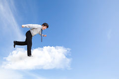 Young business man running on cloud over sky Royalty Free Stock Images