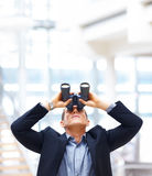 Young business man searching for opportunities. Young business man looking upwards through binoculars while standing in the office Royalty Free Stock Photography
