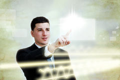 Young business man selecting a touch screen button. Young business man confidently selecting a button on a touch screen Stock Image