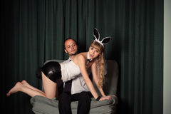 Young business man with sexy woman in bunny costume Stock Photo