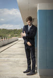 Young business man shaking off the dirt. Young man cleaning the suite on roof top Stock Image