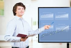 Young business man shows on the monitor charts Royalty Free Stock Images