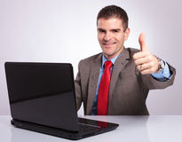 Young business man shows thumb up from behind laptop Stock Images