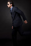 Young business man side view. In isolated black background royalty free stock photos
