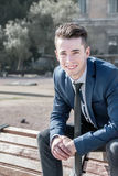 Young business man sitting on a bench in the street Stock Photos
