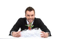 Young business man sitting and holding cut paper. Smiling guy with shredded paper and green plant Stock Photo