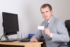 Young business man sitting in office and showing visiting card Royalty Free Stock Images