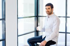 Young business man sitting on a stool in office Stock Photography