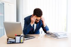 Young Handsome Businessman Has Headache. Young - Business Man Sitting At Workplace - In office Royalty Free Stock Image