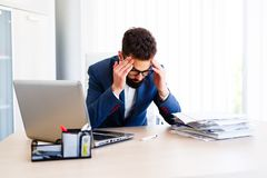 Young Handsome Businessman Has Headache. Young - Business Man Sitting At Workplace - In office Stock Image