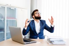 Young Businessman Has Very Stressful Day At Work. Young Business Man Sitting At Workplace - In office Stock Photo