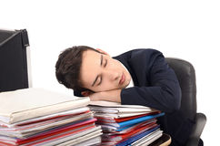 Young business man sleeping on a stack of paper work. Royalty Free Stock Photography