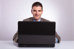Young business man smiles from behind laptop Royalty Free Stock Photo