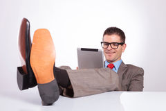 Young business man smiles at tablet, with feet on desk Stock Photography
