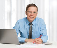 Young business man smiling. In office Royalty Free Stock Images