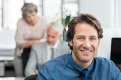 Young business man smiling. Close up face of handsome young businessman smiling in office. Portrait of a young broker sitting at office and looking at camera Stock Images
