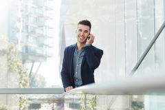 Young business man smiling with mobile phone. Portrait of young business man smiling with mobile phone Stock Photo