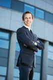 Young business man smiling outdoors with arms crossed Royalty Free Stock Image
