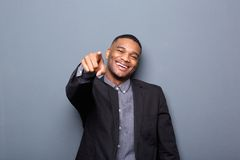 Young business man smiling and pointing finger. Portrait of a young business man smiling and pointing finger on gray background Stock Image