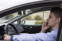 Young business man speaking on his phone inside car Stock Photography