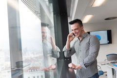 Young business man speaking on smart phone at office stock image