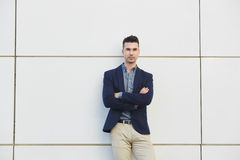 Young business man standing against white wall with arms crossed Royalty Free Stock Photography