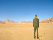 Young business man standing in desert Stock Photos