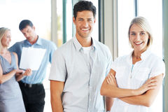 Young business man standing with female colleague Stock Photo