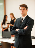 Young Business man   standing in first plain with coworkers in b Royalty Free Stock Photo